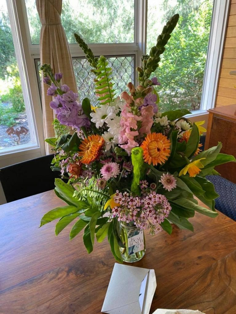 Flowers in a vase with get well card