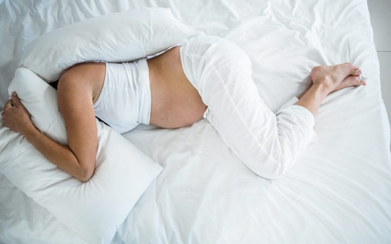 High angle view of pregnant woman with head under pillow on bed